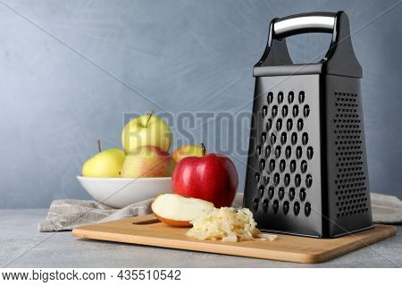 Grater And Fresh Ripe Apples On Grey Table. Space For Text