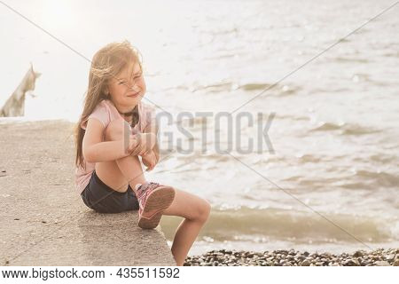 The Child Sits By The Sea And Enjoys The Sunset. A Place For A Text About Children. A Cheerful Girl