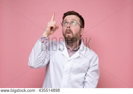 Surprised Doctor In A White Coat And Glasses Points His Finger Up And Looks Puzzled. Pink Background