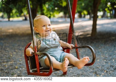White toddler wearing overalls swinging on swing at playground outdoors