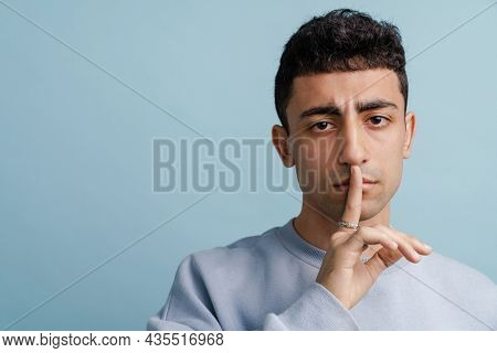Young middle eastern man showing silence gesture at camera isolated over blue background