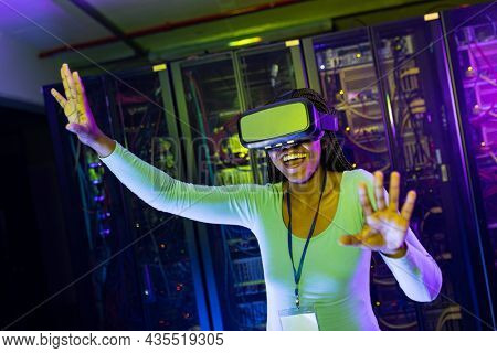 Happy african american female computer technician wearing vr headset and working in server room. digital information storage and communication network technology.
