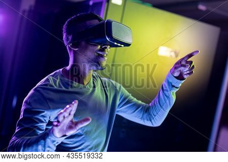 African american male computer technician wearing vr headset and working in server room. digital information storage and communication network technology.