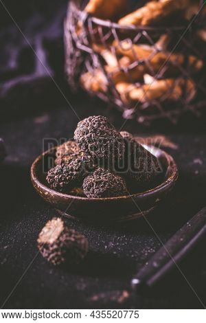 Black truffle in bowl on dark background, cooking delicacy