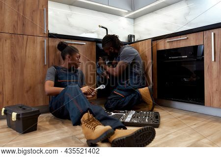 Two Plumbers On Wooden Floor Next To Kitchen Sink. African Male Technician Troubleshooting Kitchen S
