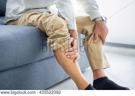 Old Man Suffering From Knee Pain Sitting Sofa In The Living Room, Elderly Man Suffering From Knee Pa