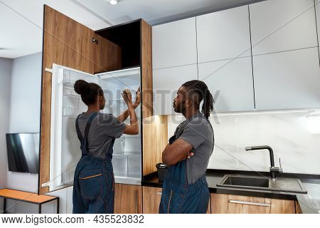Portrait Of Diverse Couple Of Appliance Service Workers, Man And Woman In Kitchen. Female Technician