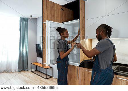 Technical Staff Repairing Refrigerator In Modern Kitchen. Female Technician And Male Apprentice In G