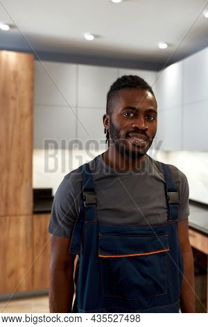 Closeup Portrait Of Young Stylish African Man In Grey T-shirt And Overalls, Posing On Modern Kitchen