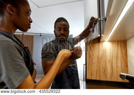 Portrait Of Multiracial Woman And Man In Overalls Fixing White Cupboard Doors. Handyman Fixing Hinge