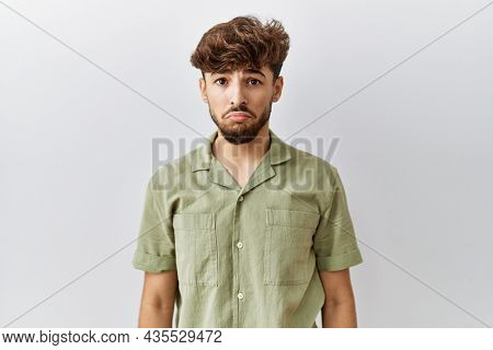 Young arab doctor man standing over isolated background depressed and worry for distress, crying angry and afraid. sad expression.