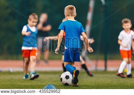 Happy School Kids Playing Football Game On School Field. Boys Kicking Soccer Ball On Artificial Gras