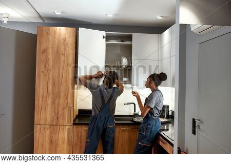 Back View Experienced Handyman Fixing Cupboard Door In Modern Kitchen. Young Lazy Apprentice Passive