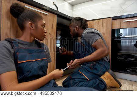 Portrait Of Professional Male African American Plumber With Young Female Apprentice Sitting On Floor