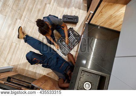 Overhead Shot Of Professional Male Plumber Lying On Wooden Floor In Kitchen, Fixing Sink Leak. Femal