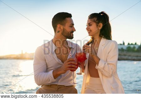 Delighted Hispanic Couple In Love Chilling On Promenade With Cold Summer Cocktails While Looking At