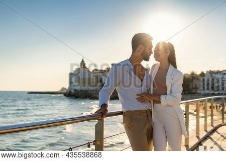 Glad Loving Hispanic Couple In Stylish Clothes Standing Near Railing On Embarkment While Embracing A