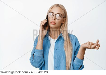 Image Of Thoughtful Woman In Glasses Talking On Mobile Phone And Shrugging, Looking Puzzled During A