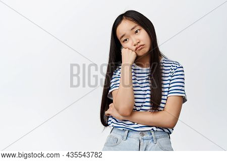 Sad And Gloomy Asian Girl Looks Lonely, Sulking And Sighing Disappointed, Standing Uneasy Against Wh