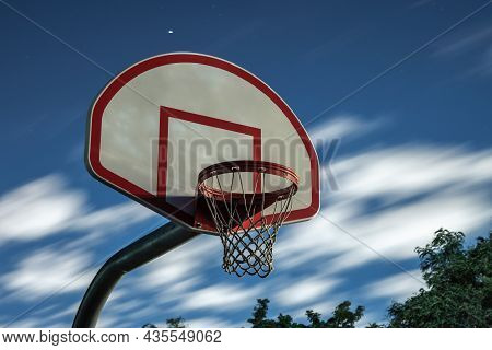 A Long Exposure Photograph Of A Dirty Orange And White Playground Basketball Hoop, Rim And Net With