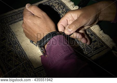 Man Putting On A Watch. Adjusts The Strap.