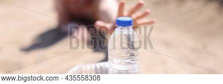 Male Hands Reaching For Plastic Water Bottle In Desert Closeup
