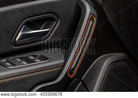 Car Door Handle With Power Window Control. Dark Leather Interior Of Modern Car. Dark Black And Orang