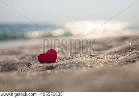 Small Red Heart On The Sand Against The Background Of Bokeh From The Glare Of The Sea. Selective Foc