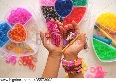 Loom For Weaving Toy Bracelets From Elastic Bands In The Hands Of A Girl. A Popular Hobby For Childr