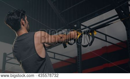 Muscular Man During Exercise Training Workout Bodyweight With Suspension Straps Trx Pull Ups Trainin