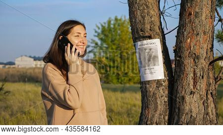 Smiling Woman In Hoodie Dials Number From Missing Dog Poster Hanging On Tree Trunk To Inform Owners
