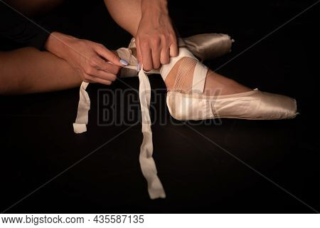 Beautiful Legs Of Young Ballerina Who Puts On Pointe Shoes At Black Floor Background. Ballet Practic