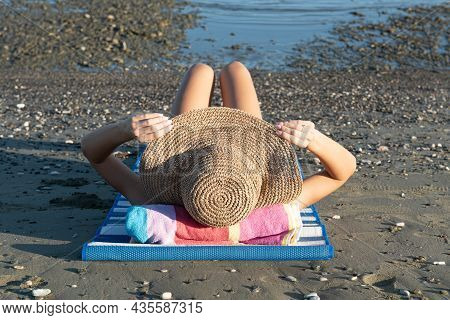 Young Unrecognized Caucasian Woman Wearing A Hat Reasting On The Beach. Summer Vacations, Relaxing O