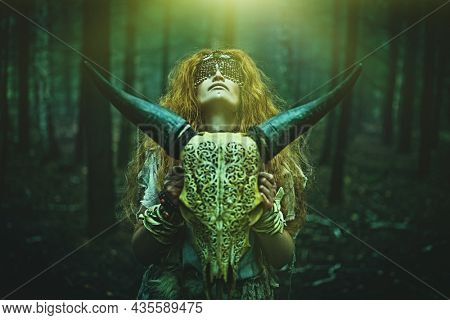 Female shaman with a mask on her eyes doing a mysterious ritual holding an animal skull in her hands. Dark gloomy forest background. Black magic concept, fantasy. Paganism. Halloween.