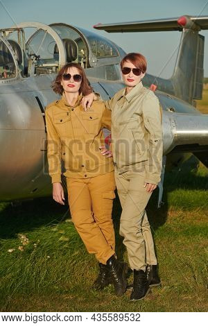 Full length portrait of two beautiful professional female commercial aviation pilots in uniform and sunglasses posing in front of their plane. Aviation.