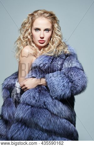 Fur coat fashion. Portrait of a beautiful woman with curly blonde hair and elegant makeup posing in an expensive silver fox coat with a bare shoulder.