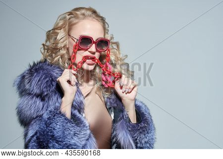 Luxury style. Portrait of a gorgeous blonde woman in an expensive silver fox fur coat and stylish red glasses. Fur coat and sunglasses fashion. Studio portrait. Copy space.