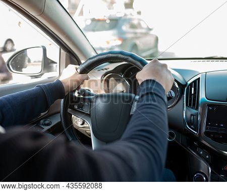 Men's Hands On The Steering Wheel Of The Car.