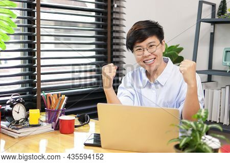Asian Woman With Short Hair Wearing Glasses Working At Home Run A Business Selling Trees Online. Smi