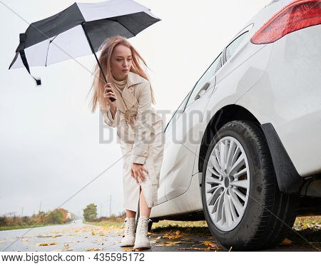 Beautiful Woman On A Road Stopped Her White Car With Punctured Car Tire. Female Driver Looking On Ty