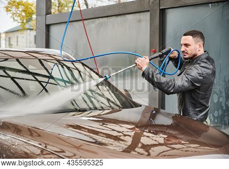 Guy Washing Dirt From Windshield Of His Auto, Using Powerful Stream Of Water. Rinsing Machine By Pre