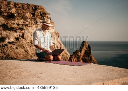 A Digital Nomad, A Man In A Hat, A Businessman With A Laptop Does Yoga On The Rocks By The Sea At Su