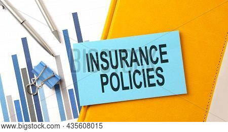 Insurance Policies Text On Sticker On The Yellow Notebook With Chart And Pen