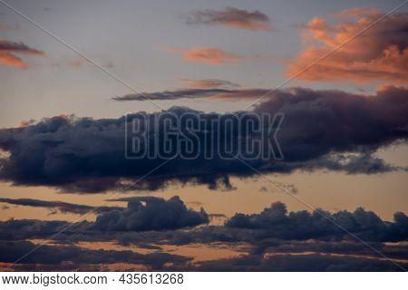 Fiery Orange Sunset Sky And Dramatic Dark Cumulus Clouds, Evening Sky. Beautiful Perfect Sky For You