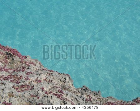 a turquoise tropical ocean and rocky cliff poster