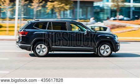 Moscow, Russia - August 2021: Black Volkswagen Atlas Is Driving Along The Street With An Autumn Urba