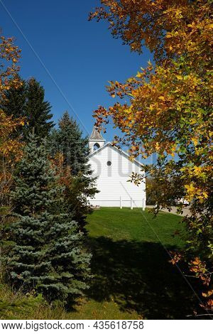 JAMESTOWN, NORTH DAKOTA - 3 OCT 2021: Pioner Church framed by trees in fall colors in Frontier Town.