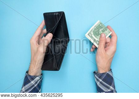 Young Man Holding An Empty Wallet And Two Dollars On A Blue Background. Financial Literacy. Bankrupt