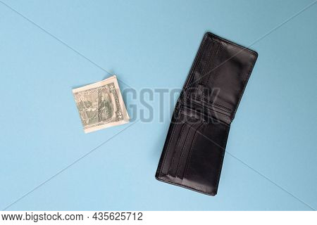 Wallet And Two Dollars Lie On A Blue Background. Bankrupt. Money Is Tight. Importance Of Savings. Fi