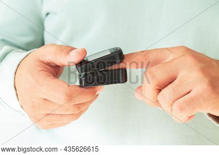 Man Checking Blood Oxygen Level With Pulse Oximeter At Home. Health Control Concept